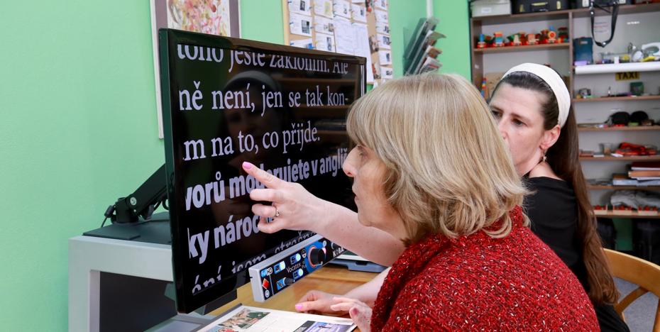 fotka jak Instruktorka učí slabozrakou klientku číst texty na počítači