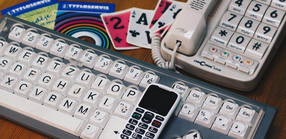 Fotka klávesnice, mobilu a pevné linky pro slbozraké