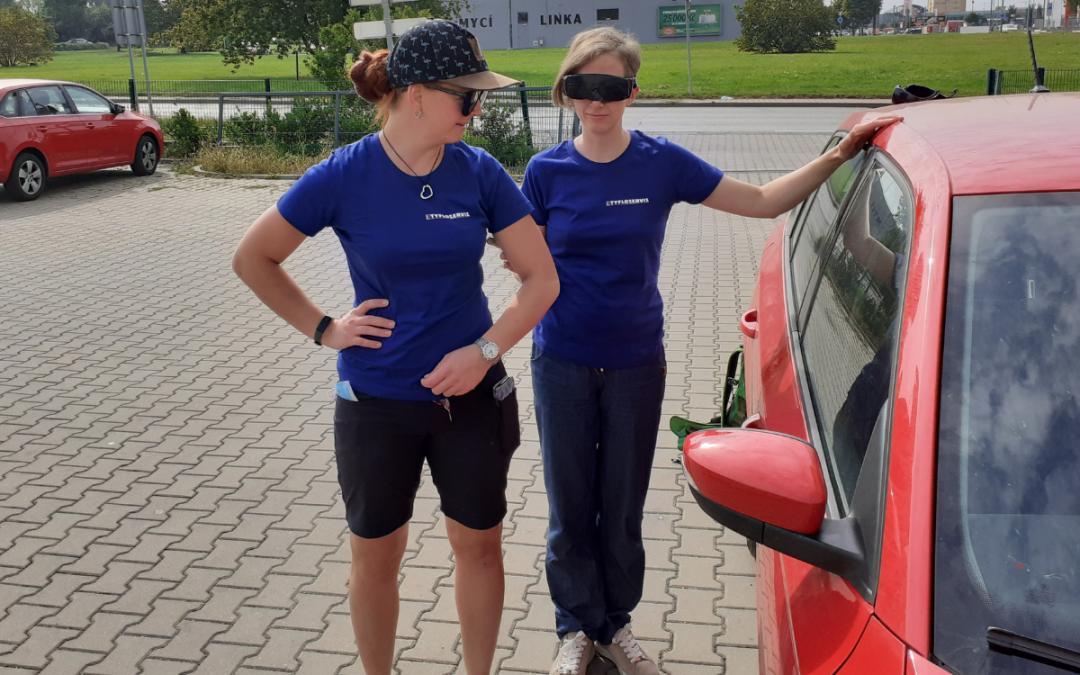 Dvě instruktorky, jedna s klapkami na očích, druhá ji provází k autu, jedná se o nácvik prostorové orientace