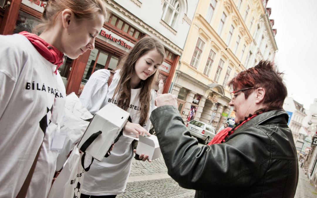 Dvě dobrovolnice a paní, která přispívá na sbírku Bílá pastelka